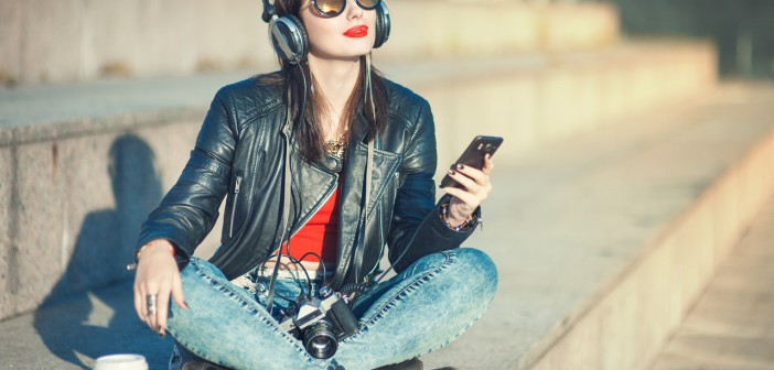 Hipster beautiful girl in leather jacket and glasses listening m